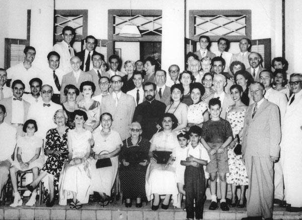 Groepsfoto Armeniërs in Batavia (rond 1954). Mevrouw Knape-Elisha's hoofd zichtbaar rechtsboven naast luik. Zoon Pieter Knape rechtsvooraan staand in korte broek met donker shirt  Bron foto: privécollectie mevrouw V. Knape-Elisha