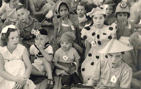 Feest aan boord: Erica met genopt jurkje, links geflankeerd door Jane (roodkapje) en rechts Wally, met hoedje met kokarde. Allemaal mijn zusjes.