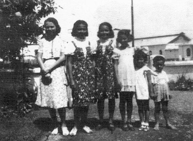De zes kinderen Jacobs (geheel rechts: Edward) in de voortuin van de woning op het terrein van de suikeronderneming Tjepiring  Foto: privécollectie Edward Jacobs