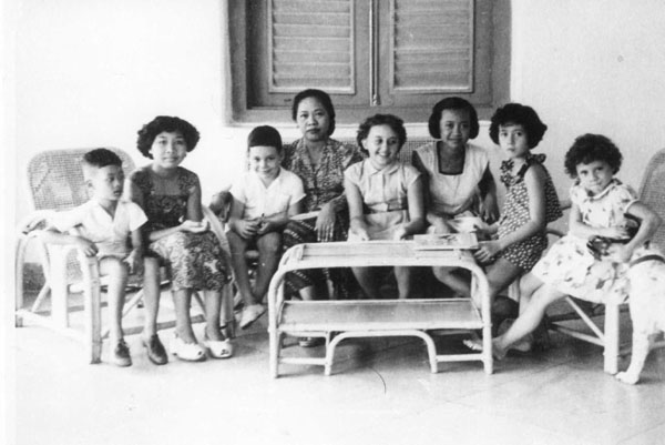 Op de voorgalerij van het pension Tanzer (gedreven door het gelijknamige echtpaar) in Djakarta, circa 1950 Zoon Pieter Knape derde van links, bij de Indonesische vrouw half op schoot, en een aantal buurtkinderen  Bron foto: privécollectie mevrouw V. Knape-Elisha
