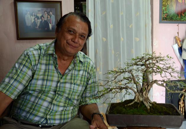 Yan Ferdinandus met een van zijn passies: bonsaibomen kweken